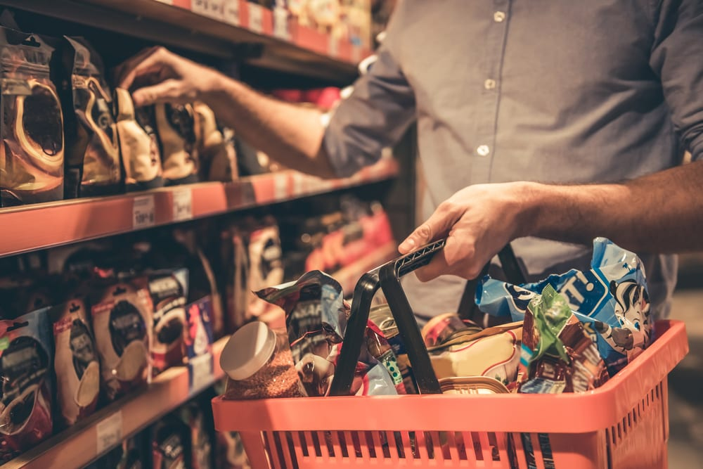 Admiring food packaging in the grocery store. A big cause of weight gain is the beautiful images on packaged food. Here are other potential causes of your weight gain.